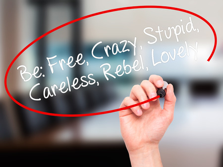 careless: Man Hand writing Be: Free, Crazy, Stupid, Careless, Rebel, Lovely with white marker on visual screen. Isolated on background. Stock Photo
