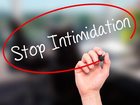 acoso laboral: Hombre de la mano escribiendo Detener la intimidaci�n con el marcador en blanco en la pantalla visual. Aislado en el fondo.