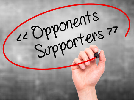 opponents: Man Hand writing Opponents - Supporters with black marker on visual screen. Isolated on background. Stock Photo