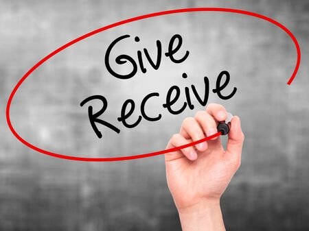 benevolent: Man Hand writing Give Receive with black marker on visual screen. Isolated on background. Stock Photo