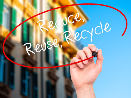 reduce reuse recycle: Man Hand writing Reduce Reuse Recycle with black marker on visual screen. Isolated on background.