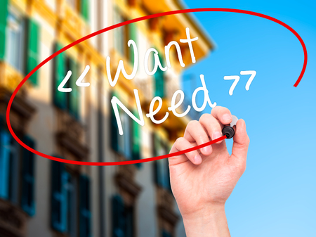 necessity: Man Hand writing Want - Need  with black marker on visual screen. Isolated on background. Stock Photo