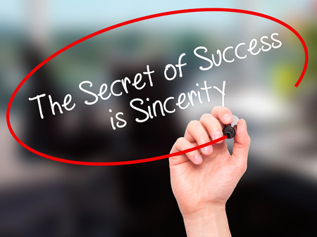 Man Hand writing The Secret of Success is Sincerity with black marker on visual screen. Isolated on background.