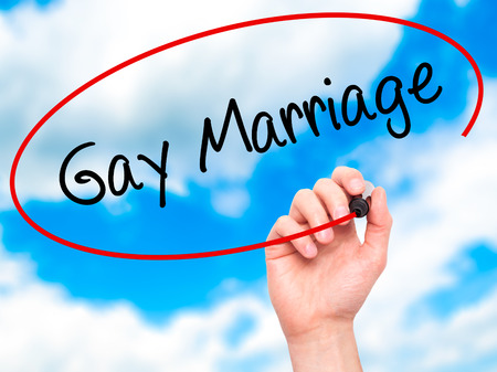 sexual orientation: Man Hand writing Gay Marriage with black marker on visual screen. Isolated on background. Business, technology, internet concept. Stock  Photo