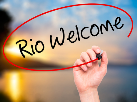 accommodating: Man Hand writing Rio Welcome with black marker on visual screen. Isolated on background. Business, technology, internet concept. Stock  Photo Stock Photo
