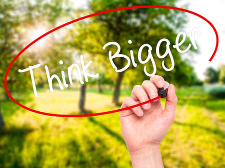 bigger: Man Hand writing Think Bigger with black marker on visual screen. Isolated on background. Business, technology, internet concept. Stock  Photo