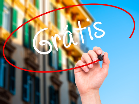 gratis: Man Hand writing Gratis with black marker on visual screen. Isolated on background. Business, technology, internet concept. Stock  Photo