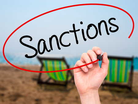 sanctioned: Man Hand writing Sanctions with black marker on visual screen. Isolated on background. Business, technology, internet concept. Stock  Photo