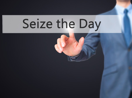 seize: Seize the Day - Businessman hand pressing button on touch screen interface.