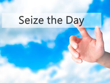 seize: Seize the Day - Hand pressing a button on blurred background concept