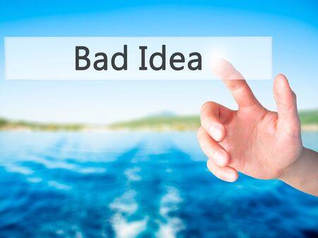 bad idea: Bad Idea - Hand pressing a button on blurred background concept