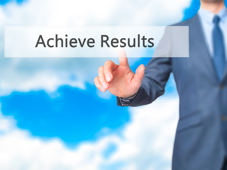 achieve: ACHIEVE RESULTS - Businessman hand pressing button on touch screen interface. Stock Photo