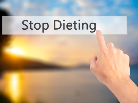 not painted: Stop Dieting - Hand pressing a button on blurred background concept . Business, technology, internet concept. Stock Photo