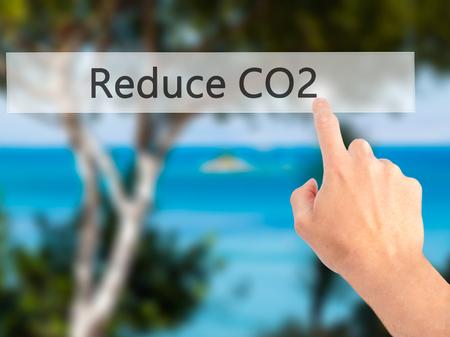 radiacion solar: Reduce CO2 - Hand pressing a button on blurred background concept . Business, technology, internet concept. Stock Photo Foto de archivo