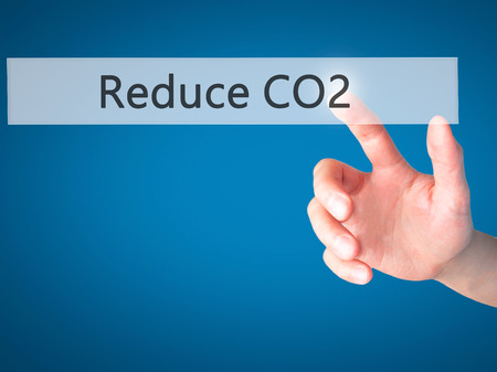 thermal pollution: Reduce CO2 - Hand pressing a button on blurred background concept . Business, technology, internet concept. Stock Photo Stock Photo