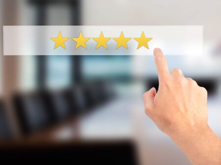 five star: Five star rating - Hand pressing a button on blurred background concept . Business, technology, internet concept. Stock Photo