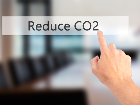 CO2 emissions: Reduce CO2 - Hand pressing a button on blurred background concept . Business, technology, internet concept. Stock Photo Stock Photo