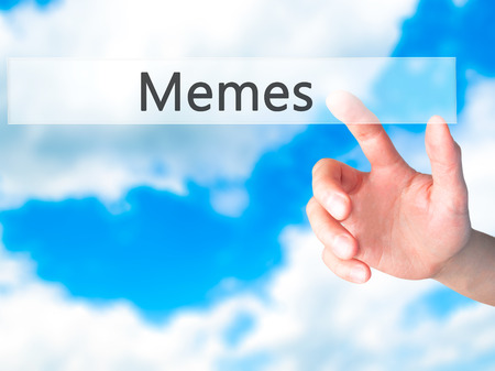 memes: Memes - Hand pressing a button on blurred background concept . Business, technology, internet concept. Stock Photo Stock Photo