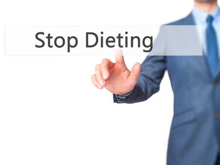not painted: Stop Dieting - Businessman hand pressing button on touch screen interface. Business, technology, internet concept. Stock Photo