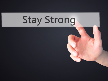 Stay Strong - Hand pressing a button on blurred background concept . Business, technology, internet concept. Stock Photo