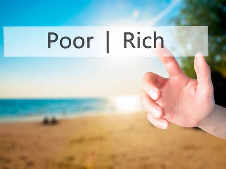 Poor  Rich - Hand pressing a button on blurred background concept . Business, technology, internet concept. Stock Photo Stock Photo