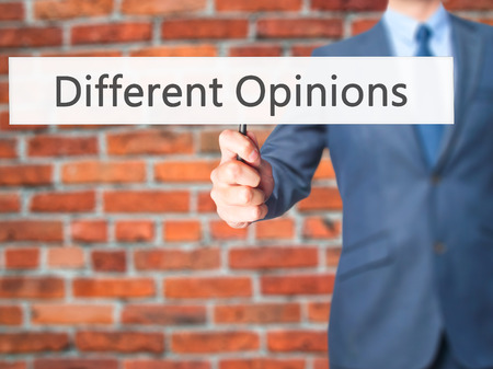 opinions: Different Opinions - Businessman hand holding sign. Business, technology, internet concept. Stock Photo