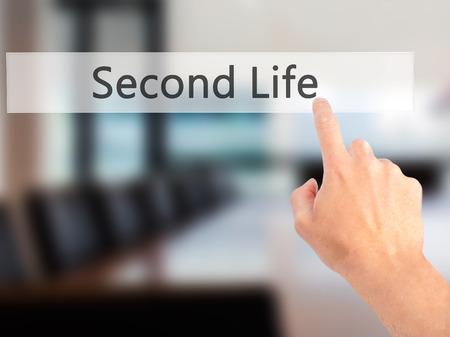 cronologia: Second Life - Mano presionando un bot�n en concepto de fondo borroso. Negocios, la tecnolog�a, el concepto de internet. Foto de stock