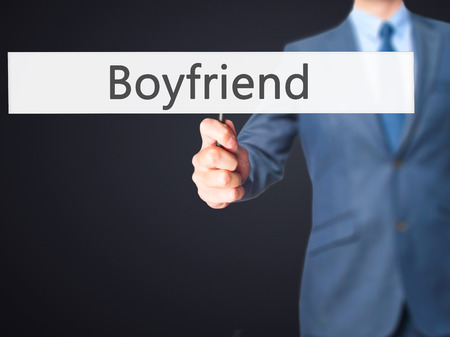heartbreak issues: Boyfriend- Businessman hand holding sign. Business, technology, internet concept. Stock Photo