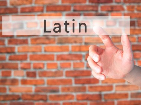 transnational: Latin - Hand pressing a button on blurred background concept . Business, technology, internet concept. Stock Photo