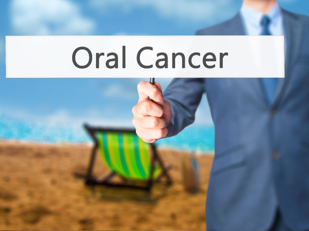 oral cancer: Oral Cancer - Businessman hand holding sign. Business, technology, internet concept. Stock Photo