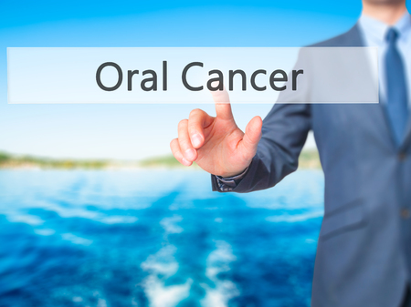 oral cancer: Oral Cancer - Businessman hand pressing button on touch screen interface. Business, technology, internet concept. Stock Photo Stock Photo