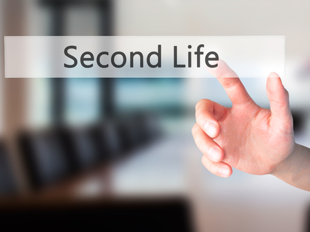 cronologia: Second Life - Hand pressing a button on blurred background concept . Business, technology, internet concept. Stock Photo
