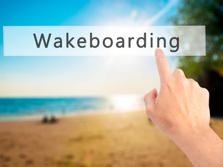 wakeboarding: Wakeboarding - Hand pressing a button on blurred background concept . Business, technology, internet concept. Stock Photo