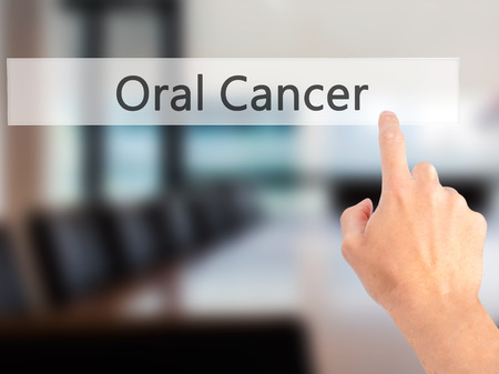 oral cancer: Oral Cancer - Hand pressing a button on blurred background concept . Business, technology, internet concept. Stock Photo