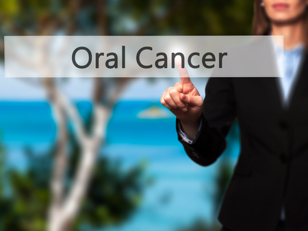oral cancer: Oral Cancer - Businesswoman hand pressing button on touch screen interface. Business, technology, internet concept. Stock Photo