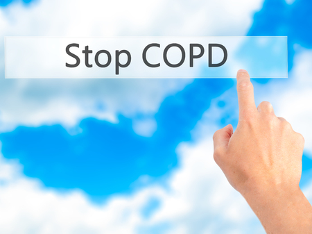 to warn: Stop COPD - Hand pressing a button on blurred background concept . Business, technology, internet concept. Stock Photo Stock Photo