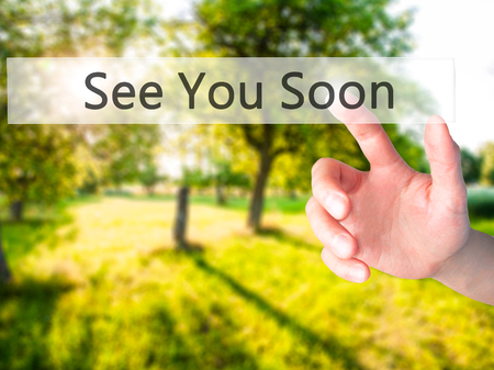 See You Soon - Hand pressing a button on blurred background concept . Business, technology, internet concept. Stock Photo Stock Photo