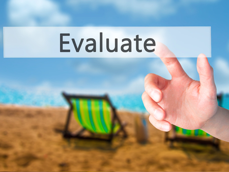 performance appraisal: Evaluate - Hand pressing a button on blurred background concept . Business, technology, internet concept. Stock Photo