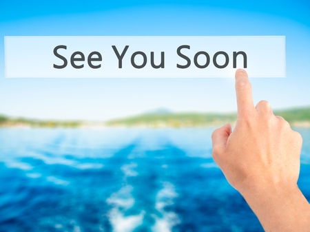 See You Soon - Hand pressing a button on blurred background concept . Business, technology, internet concept. Stock Photo Foto de archivo