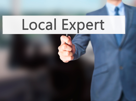 renown: Local Expert - Businessman hand holding sign. Business, technology, internet concept. Stock Photo