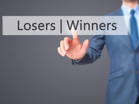 harass: Winners  Losers - Businessman hand pressing button on touch screen interface. Business, technology, internet concept. Stock Photo