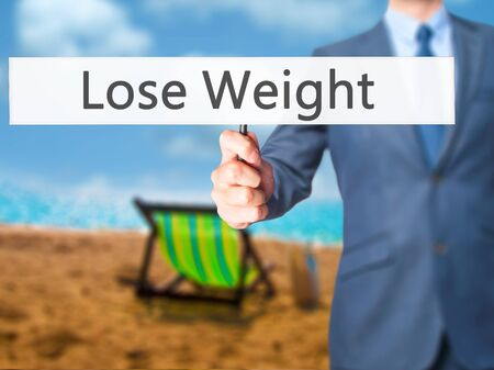 weightloss plan: Lose Weight - Businessman hand holding sign. Business, technology, internet concept. Stock Photo Stock Photo
