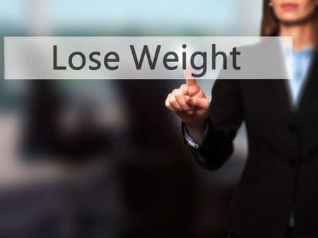 Lose Weight - Businesswoman hand pressing button on touch screen interface. Business, technology, internet concept. Stock Photo