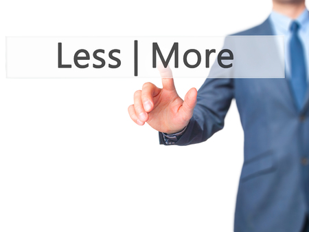 Less  More - Businessman hand pressing button on touch screen interface. Business, technology, internet concept. Stock Photo