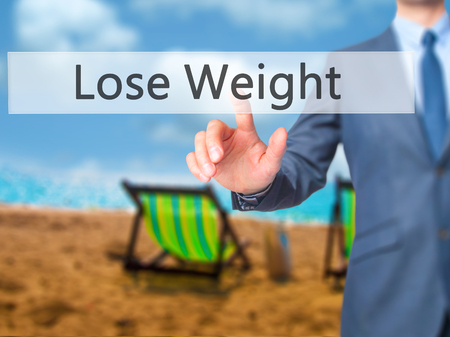weightloss plan: Lose Weight - Businessman hand pressing button on touch screen interface. Business, technology, internet concept. Stock Photo
