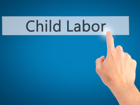 slave labor: Child Labor - Hand pressing a button on blurred background concept . Business, technology, internet concept. Stock Photo