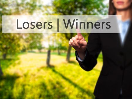 harass: Winners  Losers - Businesswoman hand pressing button on touch screen interface. Business, technology, internet concept. Stock Photo