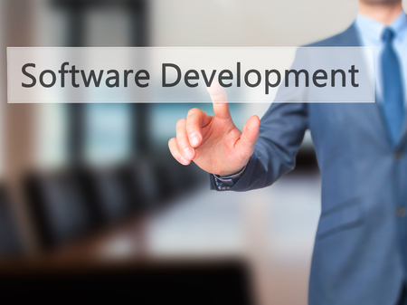 Software Development - Businessman hand pressing button on touch screen interface. Business, technology, internet concept. Stock Photo Stock Photo