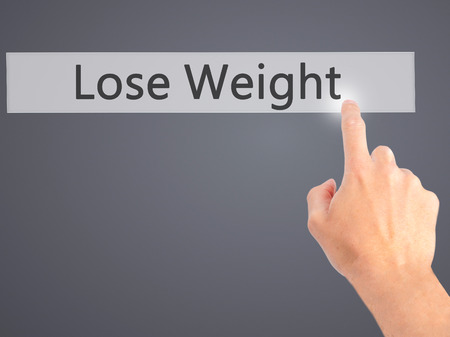 weightloss plan: Lose Weight - Hand pressing a button on blurred background concept . Business, technology, internet concept. Stock Photo