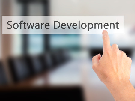 web application: Software Development - Hand pressing a button on blurred background concept . Business, technology, internet concept. Stock Photo